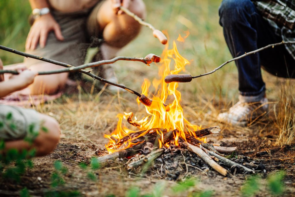 Roast sausages over a fire in nature.