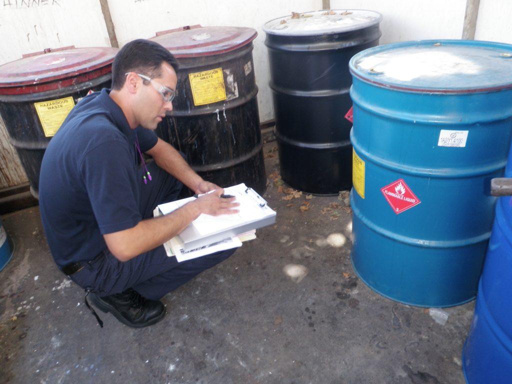Hazardous Materials inspector and hazardous waste drums.
