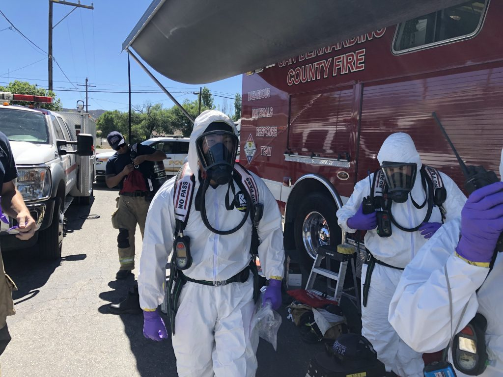 HMRT members in white hazmat in front of county fire vehicle.