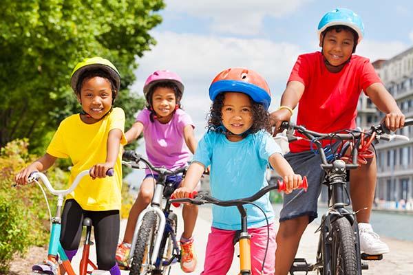 African children in safety helmets riding bikes in summer city